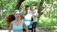 Fitness instructor leading small group of athletes while running off road