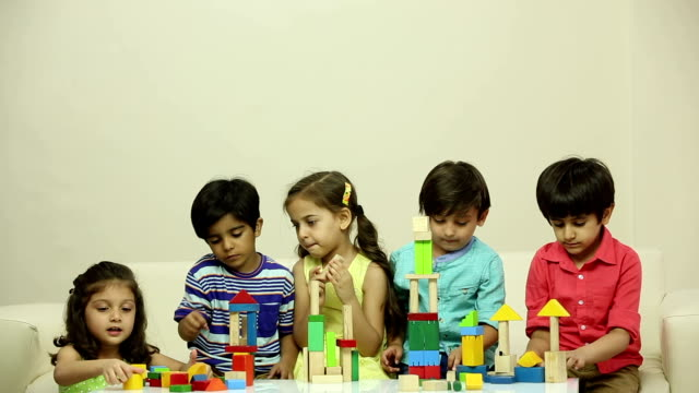 Five boys and girls making building blocks