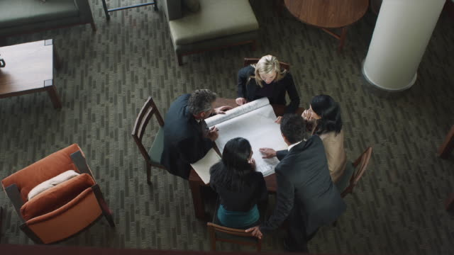 WS HA Five business associates discussing plans in workroom / Bellevue, Washington, USA