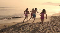 Five children running away from camera on beach.