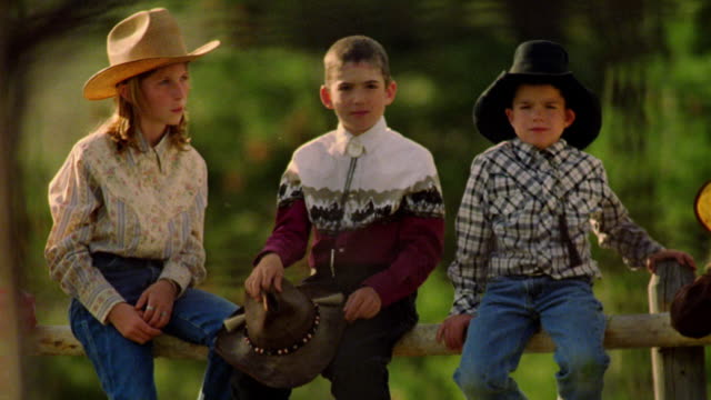 PAN PORTRAIT five children + teens in cowboy hats sitting + leaning on fence of corral / Montana