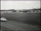 WS five compact cars competing in the 1960 Pure Oil Economy Trials drive by the camera on the Daytona Speedway track first is the Rambler American...