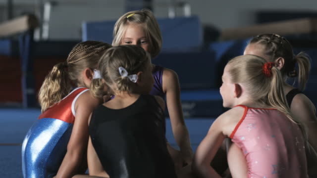 MS Five girls (6-7, 8-9) chatting and laughing in gym, Orem, Utah, USA