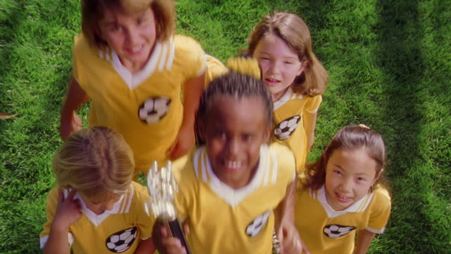 OVERHEAD PORTRAIT five girls in soccer uniforms smiling to camera, jumping up + down holding trophy