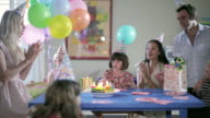 MS Five kids and three adults at table with Birthday cupcakes with lit candles,  birthday girl blowing out candles and everyone cheers / Santa Monica, CA, United States