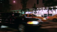 PAN Five lanes of taxis and other traffic driving past lit windows of retail store and through intersection at night / New York City, New York, United States