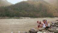 Five senior people floating paper boat in river, Ganges River, Rishikesh, Uttarakhand, India