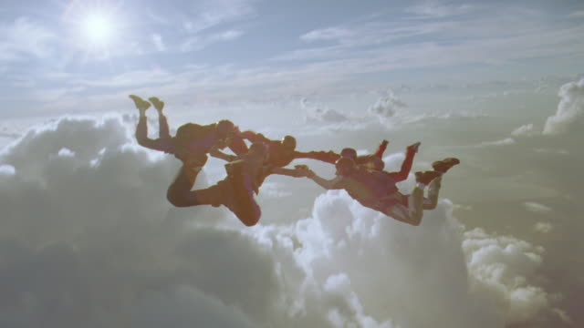 Five skydivers fall past beautiful cloud