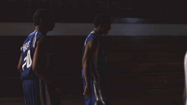 A blue team celebrates a basketball play near a red team in a basketball gym with empty bleachers.