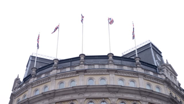 Five Union Jack flags in wind on top of building opposite Trafalgar Square in London in slow motion