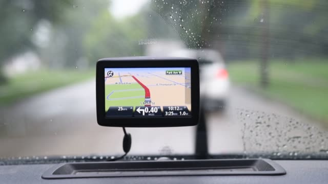 Fixed shots of a TomTom GPS navigation device mounted on the dashboard of a car as it drives towards the programmed destination near Princeton...