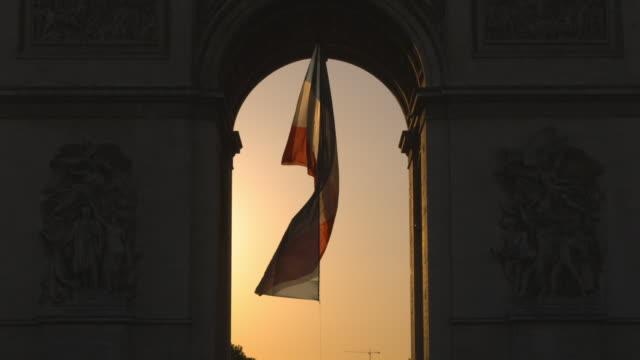 A flag flutters under the  Arc de Triomphe, Paris, France.