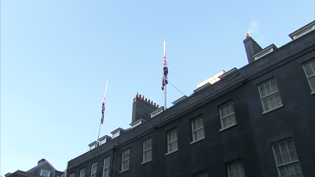 LONDON flag pole above 10 Downing Street w/ Union Jack flying at half mast in remembrance of King Abdullah