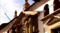 A flagpole extends from a Spanish-style building with columns and ornately-carved pediments in Bolivia. Available in HD.