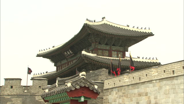 Flags fly atop a stone wall of Hwaseong Fortress.