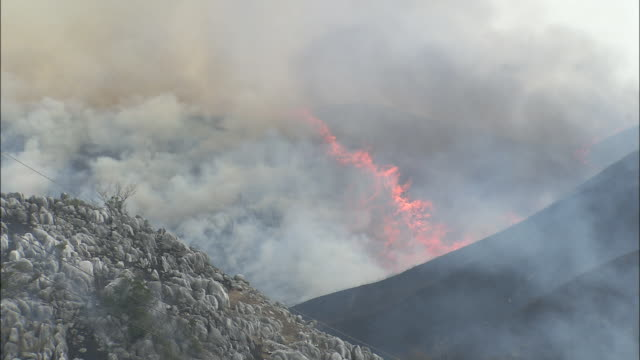 Flames and smoke spreading across mountainside as scrubland is burnt off for new growth, Hiraodai