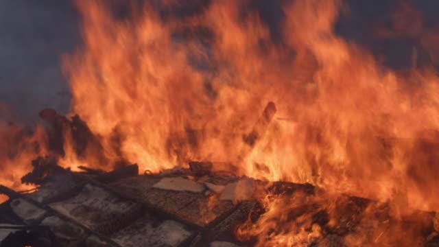 Flames blaze above a pile of rubble