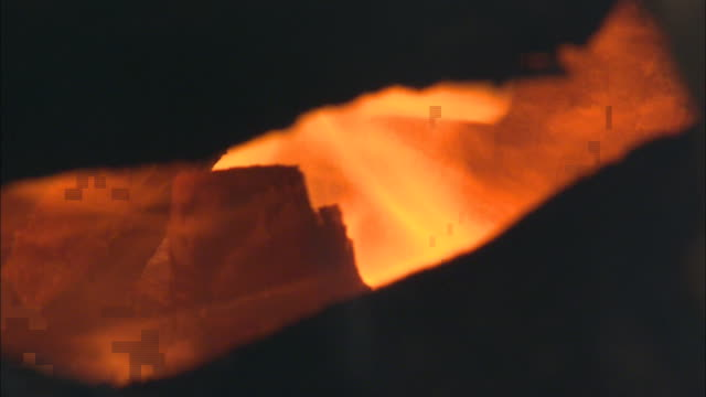 Flames burn around the logs of a cremation fire.