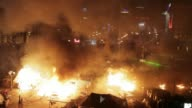 Flames engulfed the main protest camp in Kiev late Tuesday as police stormed it during the deadliest day of violence in three months of...