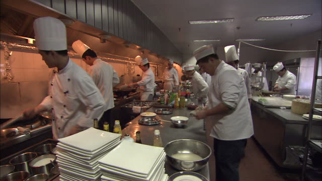 Flames flash in a busy restaurant kitchen as chefs call for ingredients from the sous chefs.