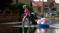 Essex Canvey Island EXT Woman dragging bags of possessions across flooded road