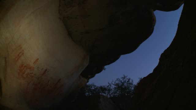 A flashlight beam illuminates hieroglyphs along rock walls. Available in HD.
