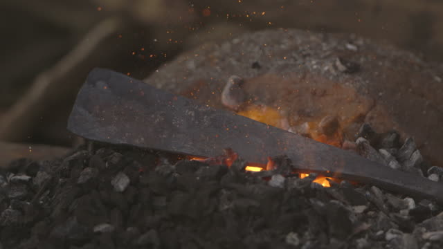 A flat metal object is heated with hot embers giving off sparks at a workshop in Sierra Leone.