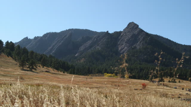 WS Flatirons rock formations landscape w/ green trees tall brown grass unidentifiable people walking up path clear blue sky