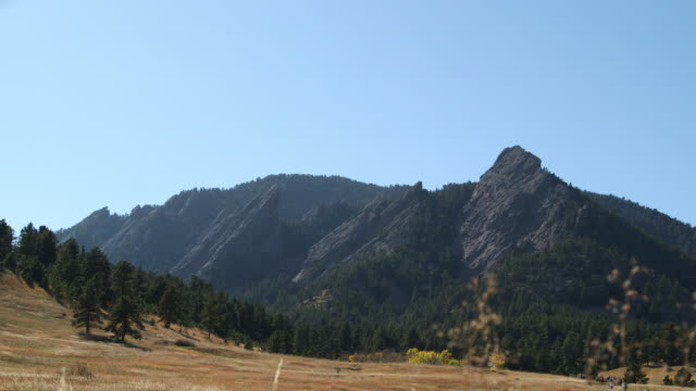 Flatirons rock formations landscape w/ green trees tall brown grass unidentifiable people walking up path clear blue sky