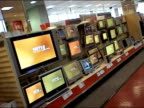 Flat-screen televisions in high definition on display in aisle of electronics store in New York City / customers and salesman walking through aisle
