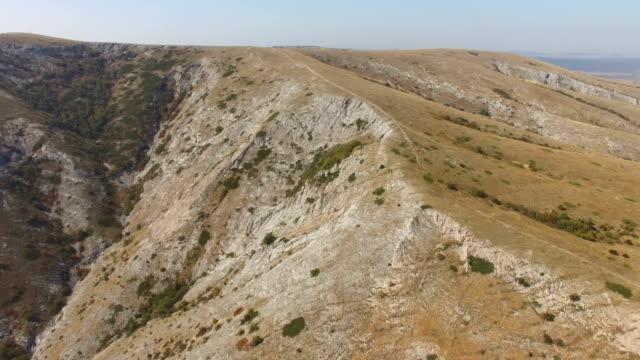 AERIAL: Flight along mountain plateau