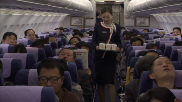 MS Flight attendant carrying tray full of cups through airplane aisle, Sichuan, China