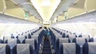 Flight attendants stow luggage in the aisles of a Bangkok Airways Co Airbus SAS A319 aircraft at Hong Kong International Airport in Hong Kong China...