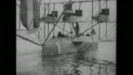 Flight crew works on airplane / pilot jumps out of plane wearing his flight gear / MS US Navy Curtiss NC4 flying boat No 1 moves in water away from...