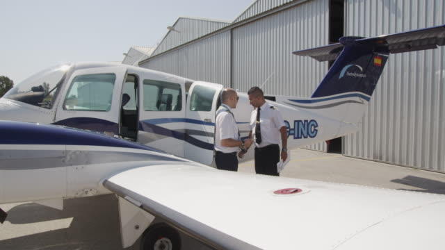 flight instructor and trainee pilot during pre flight inspection of aircraft, RED R3D 4K