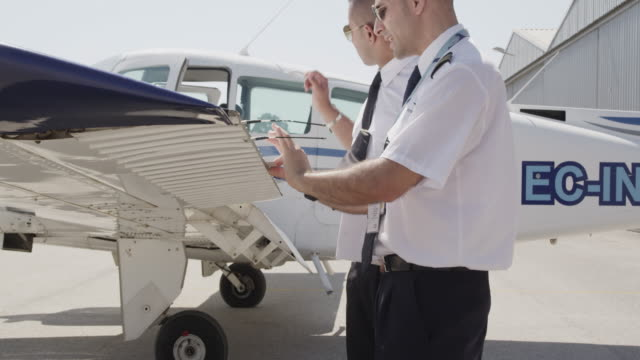 flight instructor and trainee pilot during pre flight inspection of aircraft; instructor demonstrating freedom of movement check of ailerons, RED R3D 4K