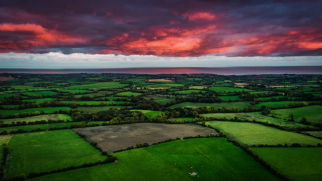 Flight over patchwork landscape with fields and farms in Ireland