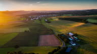 Flight over rural patchwork landscape with fields and villages in warm sunset light
