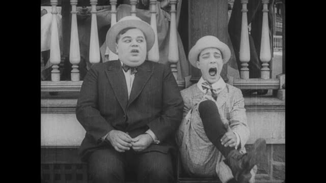 Flirting Fatty Arbuckle tricks woman into swapping places with him as he sticks a pin into Buster Keaton's leg