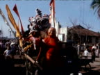 Float carrying people in fancy dress parades through market 1970