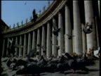 Flock of pigeons glide into land in St Peter's square basilica columns and tourists in background Rome
