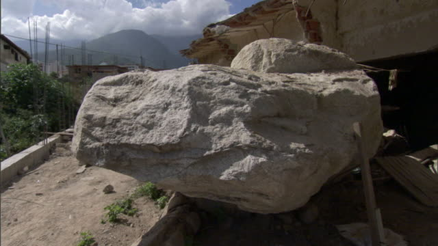 A flood damaged building has a ruined roof and boulder in front of a crumbled wall.
