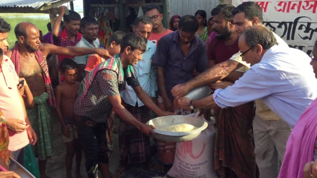 Flood victims are collecting relief supplies provided by a local political organization Gaibandha Bangladesh August 19 2017
