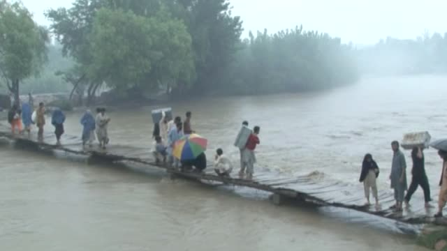 Flood victims scramble across damaged bridge in search of shelter following severe rains and flooding