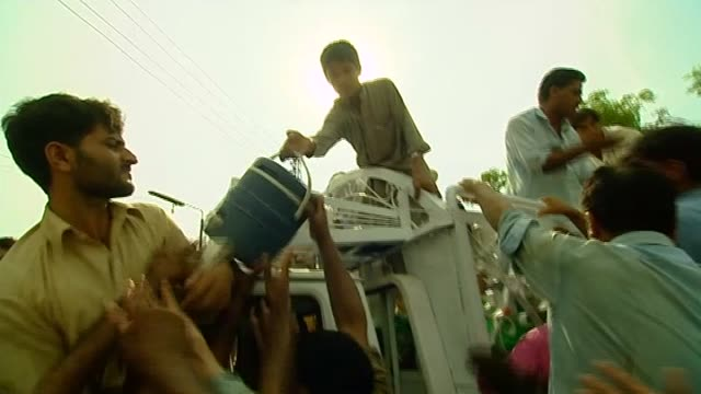Flood victims scramble for food aid distributions following severe rains and flooding within Pakistan