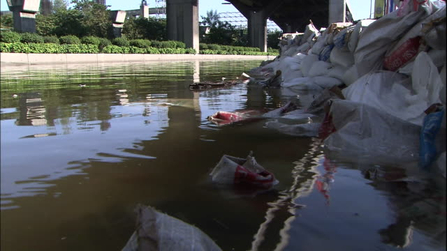 Flood water ripples against sandbags piled in the street in front of Bangkok's Don Mueang International Airport