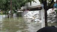 Flood waters in Thailand lap against stacks of sandbags