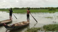 WS of flooded rice paddies in Puok Area as two men on paddleboats paddling toward middle of field / Siem Reap, Siem Reap Province, Cambodia