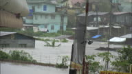 Flooded street in heavy rain w/ some buildings palms under water higher ground homes foggy BG Typhoon season flooding flood PAGASA name Pepeng...