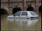 Flooded car park PAN car stranded in flood water GV Car partly submerged in flood water Swollen river flowing under bridge arch Woman wading through...